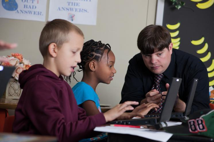 Teaching student working with two children at a computer